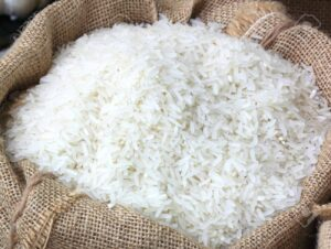 Raw long grain white rice grains in burlap bag
